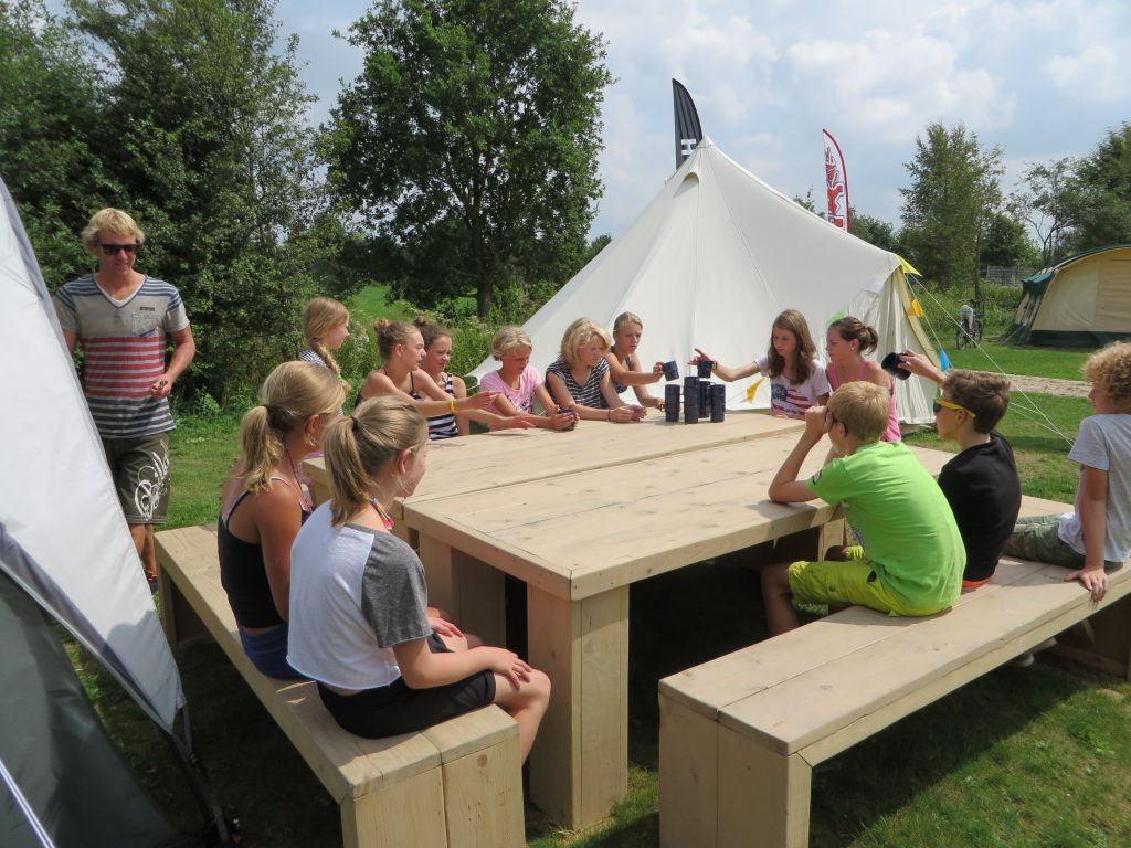 kinderen zitten aan grote picknicktafel op GroepsNatuurkampeerterrein De Jarden